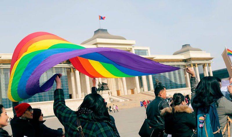 A Oulan-Bator, un petit groupe de personnes agite un grand drapeau arc-en-ciel au-dessus de leurs têtes, devant le bâtiment du Parlement.