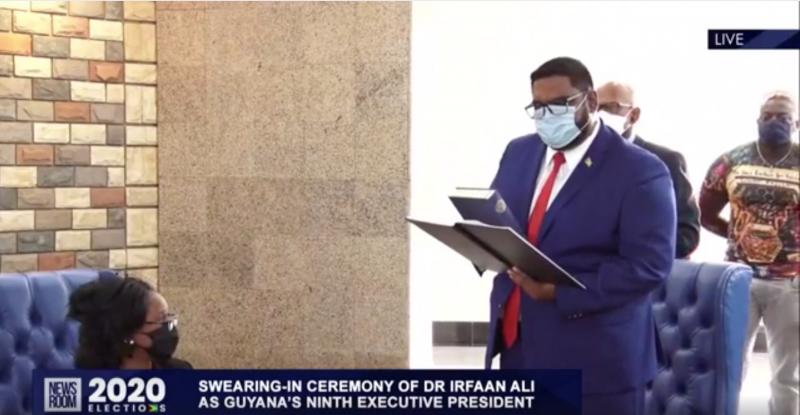 Le nouveau président du Guyana, Mohamed Irfaan Ali, prête serment sur la Bible. Il se tient debout, vêtu d'un costume bleu et portant un masque de protection faciale