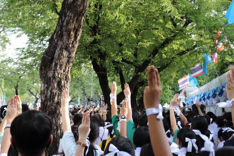 Une forêt de bras élevés, 3 doigts pointés vers le haut, lors d'une manifestation étudiante en Thaïlande.