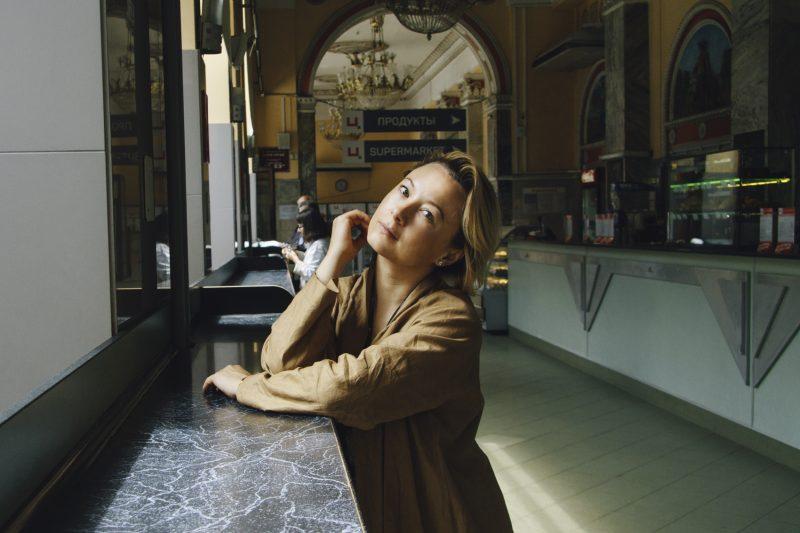La poétesse bélarussienne Valzhyna Mort pose accoudée à un comptoir dans une gare.