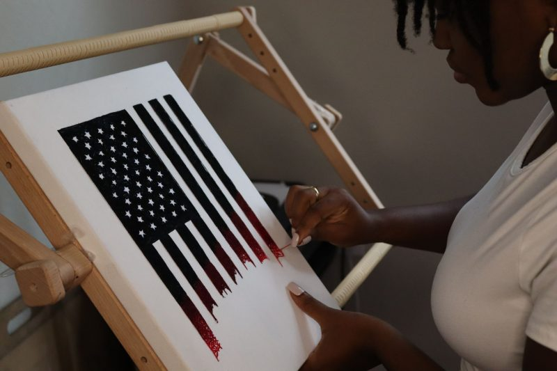 Nneka Jones, vue de profil, brode l'une des bandes verticales du drapeau des Etats-Unis sur une toile.