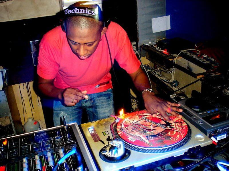 Un DJ devant ses platines et sa table de mixage, les écouteurs sur les oreilles.