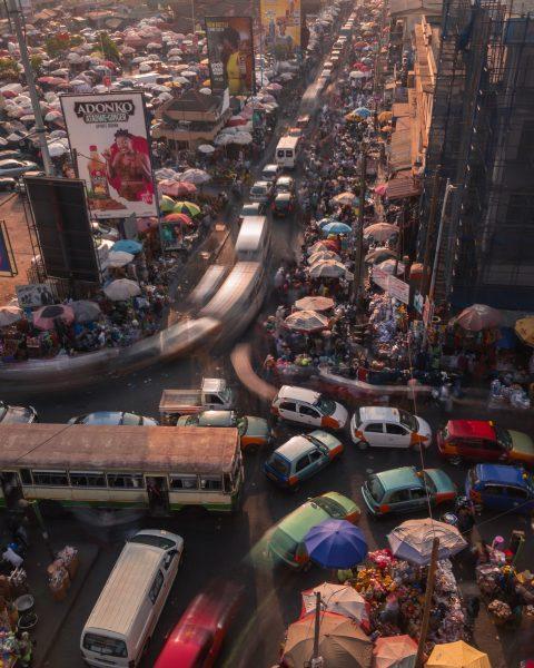 Vue surplombante sur un marché d'Accra, occupé par une foule dense et bordé par une rue embouteillée.