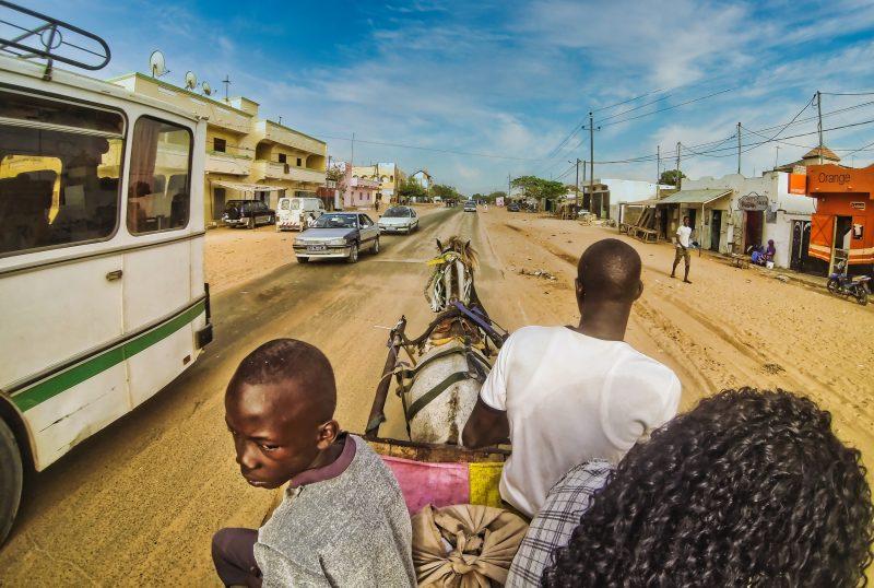 Au Sénégal, vue d'une rue couverte de sable depuis une charrette tirée par un cheval, qui croise un bus et des voitures.