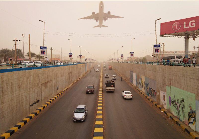 La route à quatre voies de l'aéroport de Khartoum au Soudan. Dans la brume au dessus de la route, on voit un avion décoller.