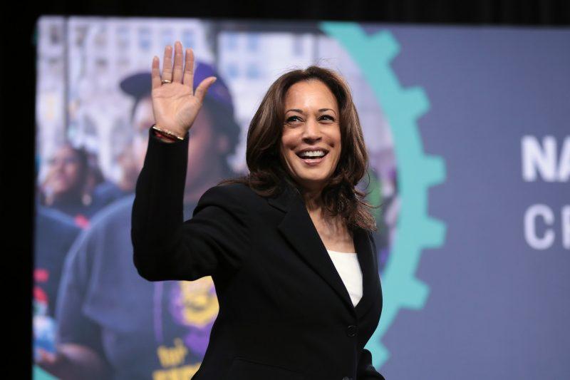 La sénatrice américaine Kamala Harris fait un salut de la main et arbore un grand sourire.
