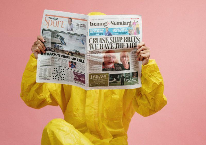Photo couleur. Une personne dans une combinaison imperméable jaune lit un journal.