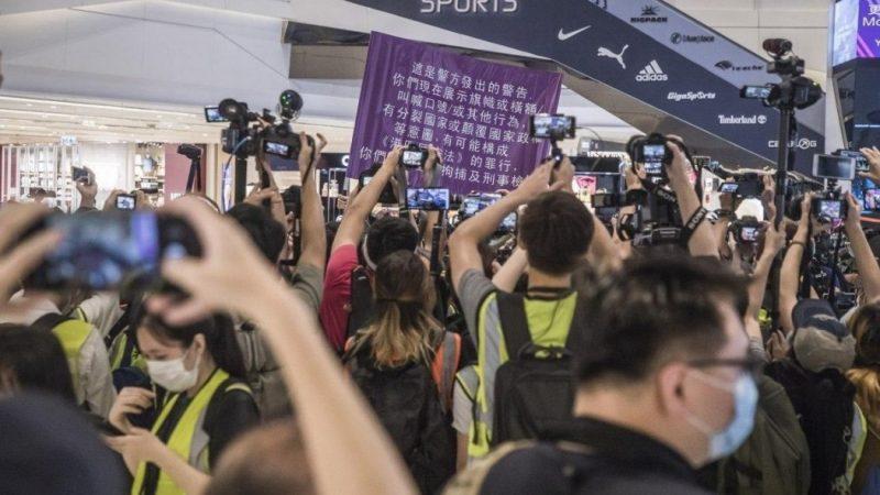 Une bannière violette, avec des inscriptions en chinois. Tout autour, une foule de photographes portant leurs appareils photo à bout de bras capturent ce moment.
