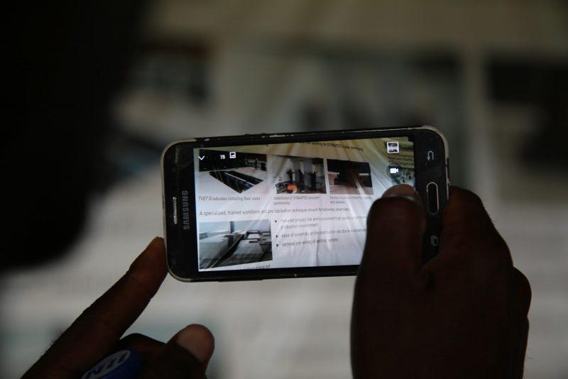 Un téléphone mobile Samsung est tenu à deux mains tandis que l'utilisateur prend en photo une affiche lors de la Semaine de la croissance verte au Rwanda.