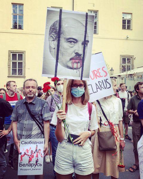Une femme portant un masque de protection faciale tient une pancarte où la bouche de Loukachenko dégouline de sang.