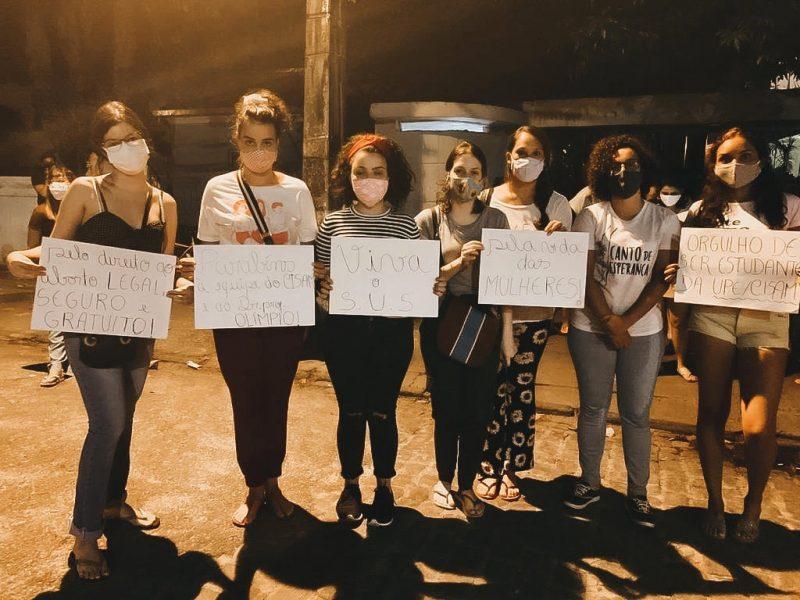 7 jeunes femmes se tiennent devant l'objectif de la caméra. Elles portent toutes un masque de protection faciale, et tiennent des affiches avec des messages en faveur de l'avortement.