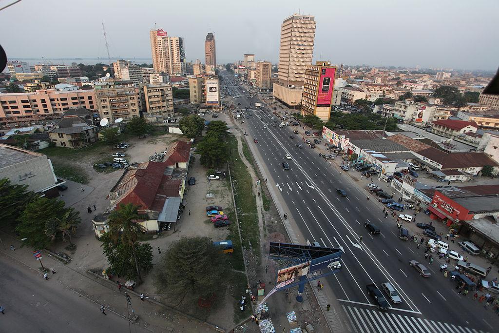 Vue surplombante du centre-ville de Kinshasa, avec une autoroute à 4x4 voies et des immeubles au fond.