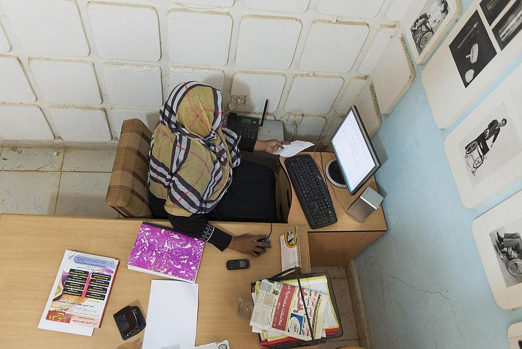 Une femme assise à un bureau consulte un ordinateur.