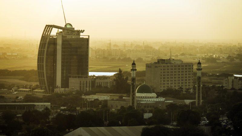 Vue de Khartoum au crépuscule. Des minarets se détachent sur fond de ciel orangé, ainsi qu'un immense building.