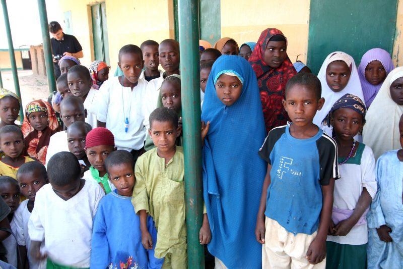 L'image montre plusieurs enfants d'origine africaine. Il y a des garcons et des filles. Les filles sont habillées avec une tenue islamique. Tous les enfants font face à la caméra. Ils sont à l'extérieur, dans une école. Dans la cour, on distingue des poteaux de couleur verte. Un des poteaux se trouve au centre de la photo, sur lequel deux enfants se tiennent.