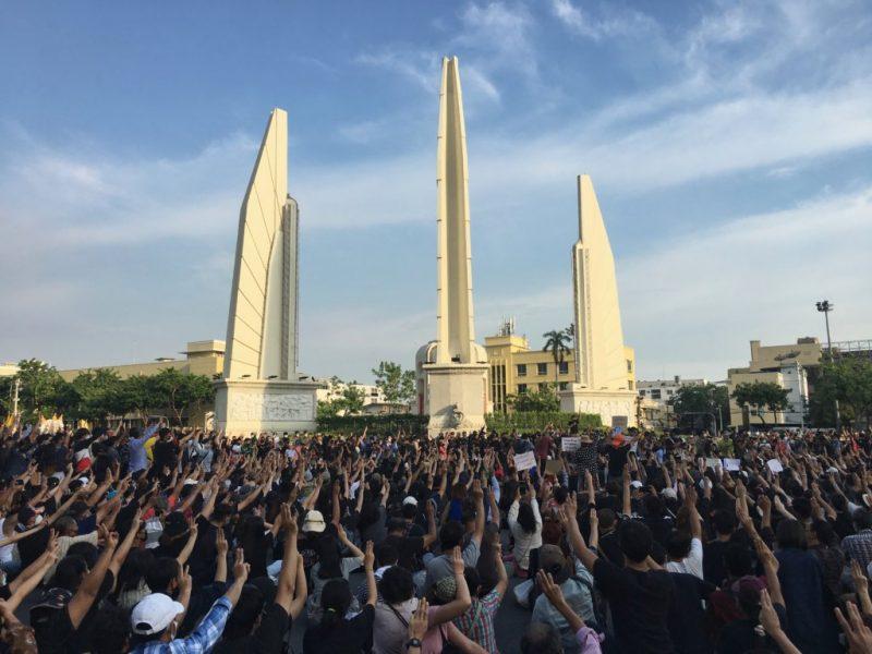 Une foule dense de jeunes thaïlandais sont rassemblé.e.s autour du monument de la démocratie à Bangkok, levant trois doigts en signe de protestation.