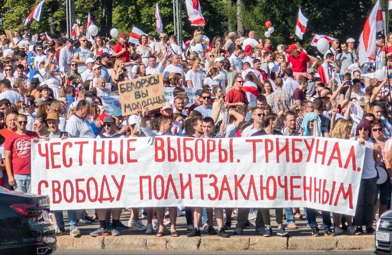Une foule de manifestants au Belarus arbore les couleurs rouge et blanche du drapeau. Au premier plan, certains tiennent une grande banderole.