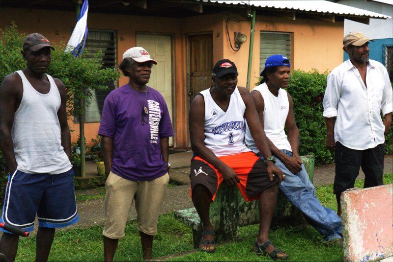 Cinq hommes se tiennent devant une maison. tous portent une casquette. Les 4 premiers portent un T-shirt et le dernier une chemise.