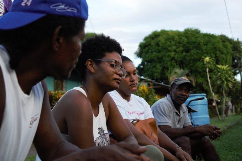 Quatre membres de la communauté Kriol assis en rang, l'air pensif et triste.