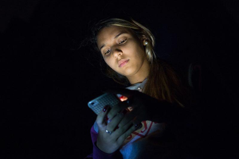Le visage d'une jeune Vénézuélienne est illuminé par son téléphone portable, le reste de l'image est dans l'ombre.