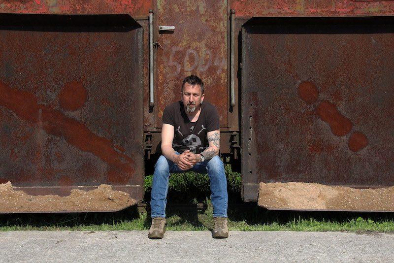 Valts Ernštreits, en t-shirt et jean, assis entre deux containers rouillés. il ades tatouages et une barbe poivre et sel.