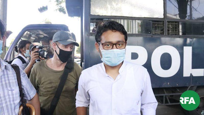 L'image montre un homme portant des lunettes et un masque de protection faciale, entouré par d'autres personnes avec un masque. Il regarde la caméra. Un photographe prend une photo, en arrière plan. On distingue le logo RFA (Radio Free Asia), à droite en bas de l'écran.