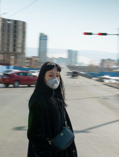Devant un paysage urbain flou, une jeune femme se tient face caméra, portant un masque facial pour se protéger de la pollution à Oulan-Bator.