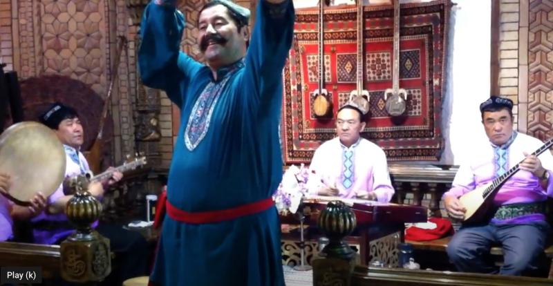 Un danseur accompagné par musiciens dans l'un des restaurants Miraj à Urumqi