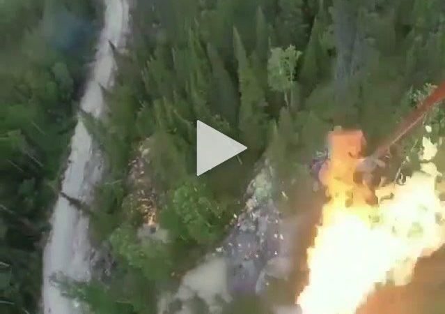 Un hélicoptère déverse du carburant enflammé sur la végétation de la forêt pour combattre l'incendie.