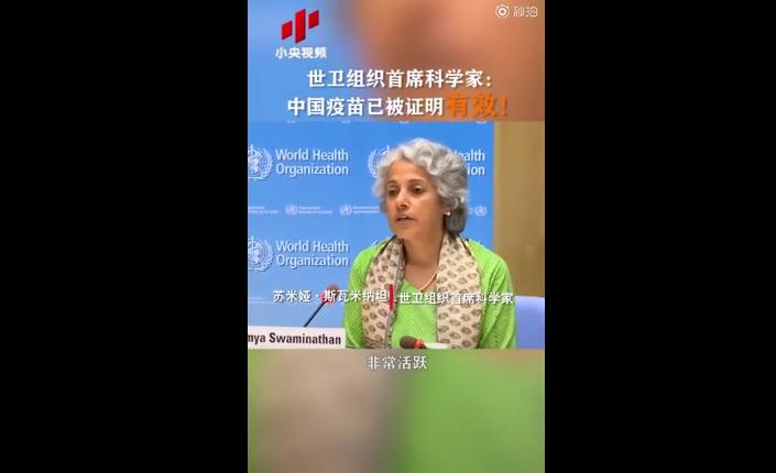 L'image est arrêtée sur le Dr. Soumya Swaminathan. Elle est assise et donne une conférence. Son nom est inscrit sur un carton posé à côté d'elle. Elle a des cheveux plutôt gris, elle porte un foulard et un pull vert. En arrière plan, on peut lire et voir le logo de WHO (OMS) et des inscriptions en chinois.