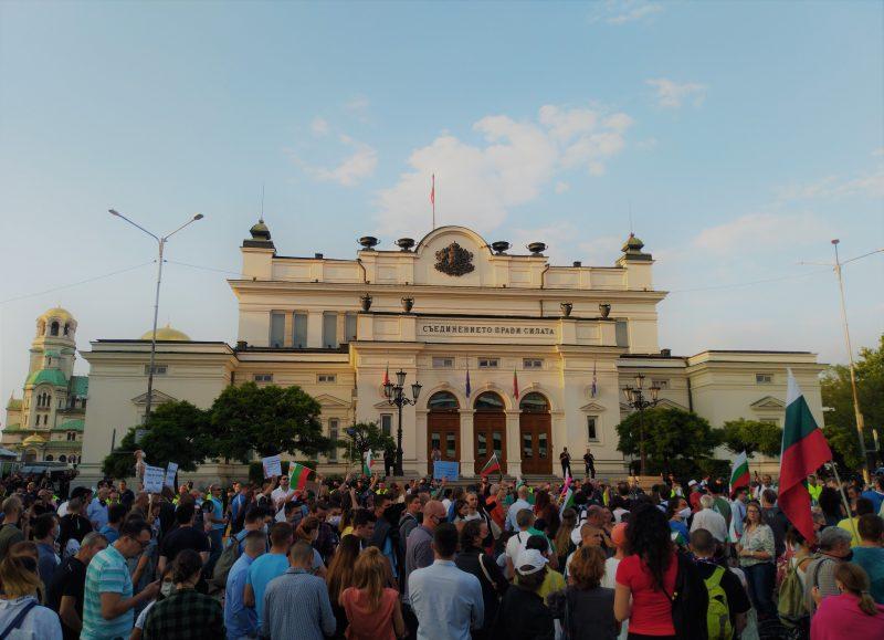 Manifestants devant le Parlement de Sofia, brandissant des drapeaux et des panneaux.