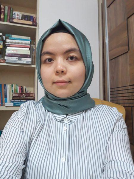 Photo de face de Fazilat Abdureshit, devant une étagère de livres. Elle porte un hijab turquoise et une chemise rayée.