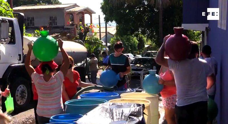 Un grand camion citerne approvisionne un quartier en eau au Salvador. Les habitants viennent se ravitailler à l'aide de jarres.