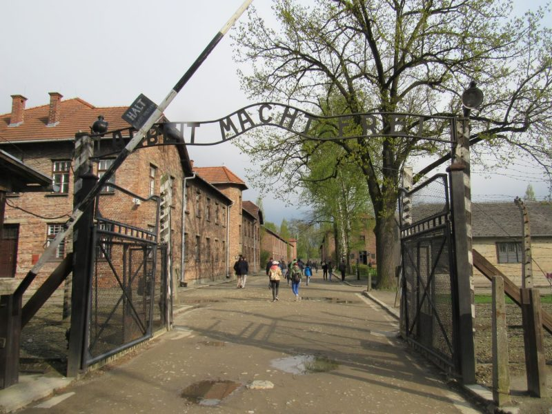 """Le portail à l'entrée du camp d'Auschwitz-Birkenau avec l'inscription en fer forgé """"Arbeut Macht Frei""""."""
