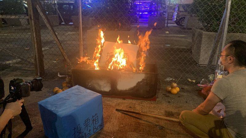"""On peut voir sur l'image un feu qui brûle dans une caisse. Un homme est accroupi, de profil, en face du feu. L'homme tient un bâton, On distingue une urne bleue avec l'inscription en chinois et en anglais, """"Ballot Box"""". Un appareil photo tenu par une main apparaît dans le cadre sans que l'on puisse voir le corps de la personne. Derrière le feu, il y a un grillage. La scène se passe de nuit, en extérieur."""