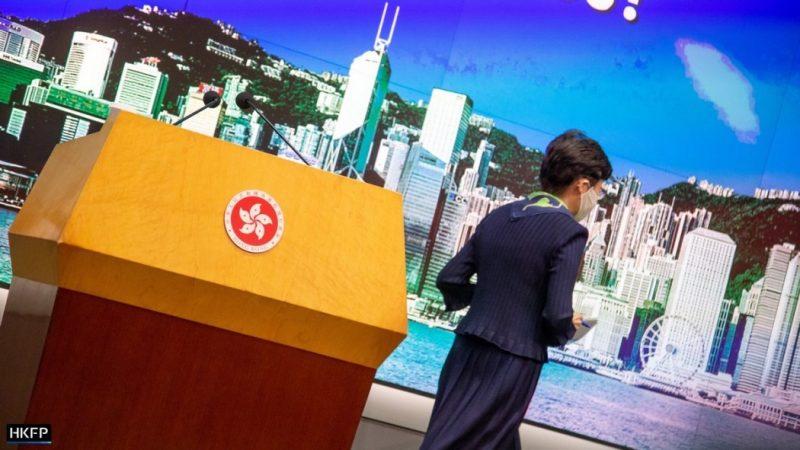 L'image, légèrement penchée sur la droite, montre Carrie Lam quittant un pupitre avec des micros, dans le cadre d'une conférence de presse. Elle est vue de profil, cheveux courts bruns, sur fond de buildings, d'océan et de montagne.