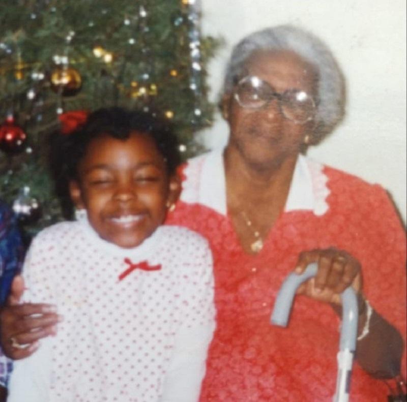Devant un sapin de Noël, une petite fille, l'auteure pose avec sa grand-mère, cheveux gris, lunettes et tenant une canne.