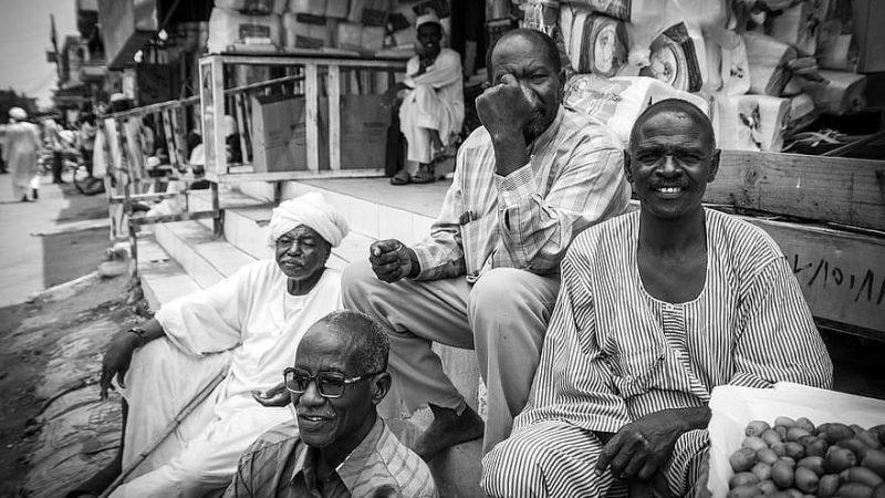 Photo en noir et blanc montrant des hommes soudanais âgés assis sur des marches, en train de passer un moment amical.