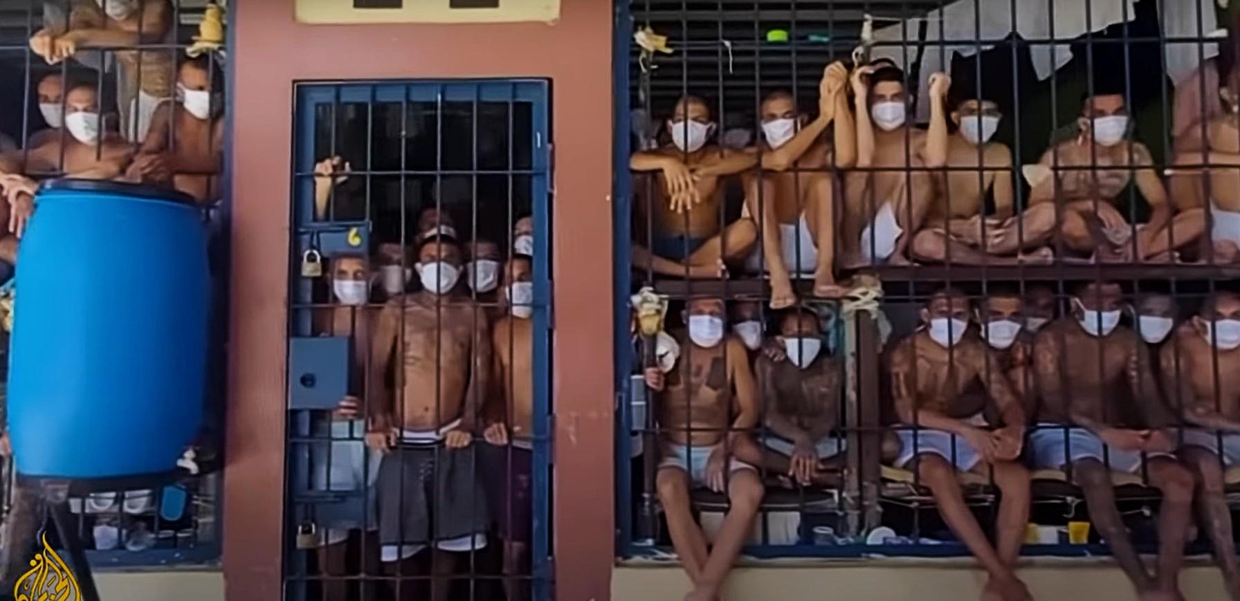 Des prisonniers sont enfermés derrière des barreaux, dans un espace très réduit. Tous portent un short et un masque blancs, et sont aggripés aux barreaux.