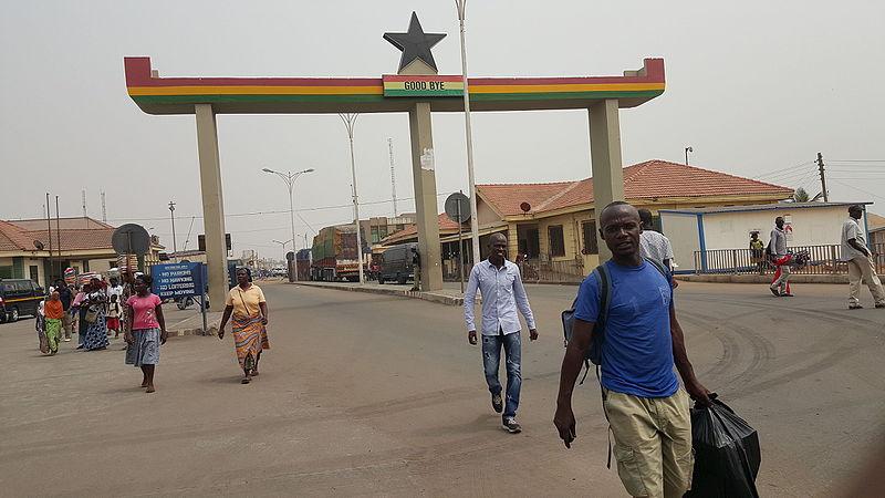 Les voyageurs traversent la frontière Ghana-Togo à pied, passant sous une arche rouge, jaune et verte surmontée d'une étoile.