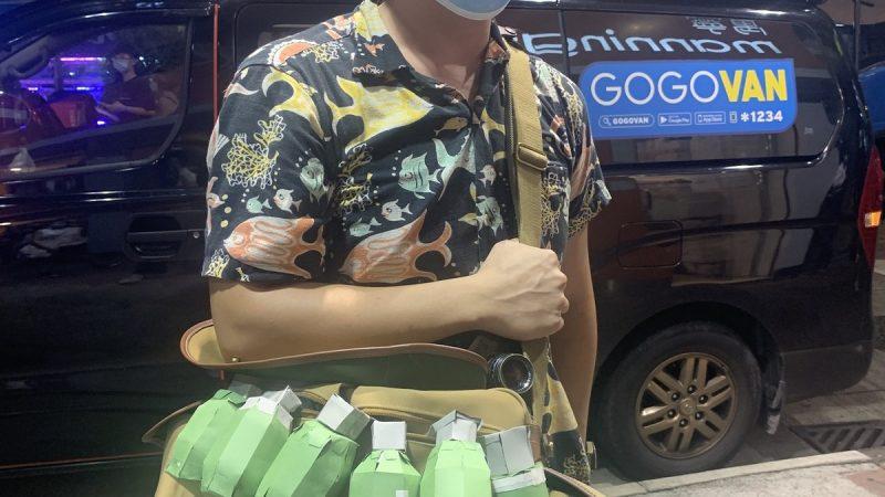 L'artiste Man Chan portant une sacoche en bandoulière sur laquelle des grenades gammon, fabriquées en papier, sont accrochées. On ne voit pas sa tête.