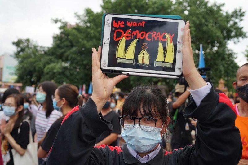 """Une jeune manifestante, portant un masque, porte à bout de bras une tablette sur laquelle on peut lire: """"nous voulons la démocratie""""."""
