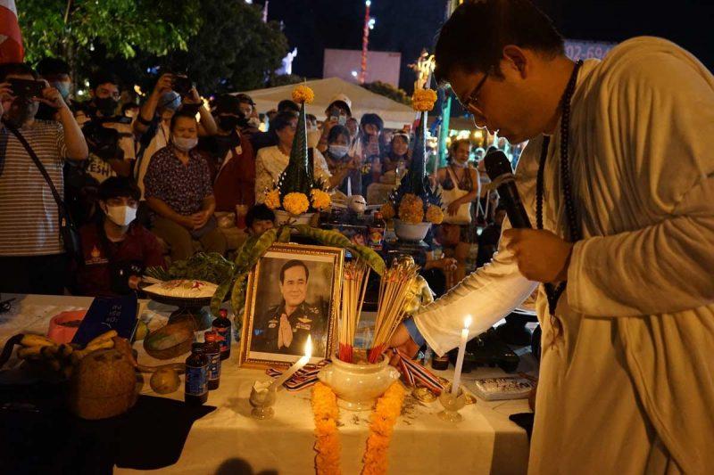 La photo du général Prayuth est posée sur une table et entourée de bâtons d'encens, de guirlandes de fleurs et de bougies, pour un rituel factice.
