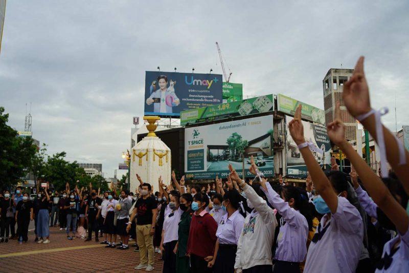 Des lycéens de Khon Kaen en uniforme lèvent 3 doigts vers le ciel, un symbole de résistance du mouvement de protestation pro-démocratie.