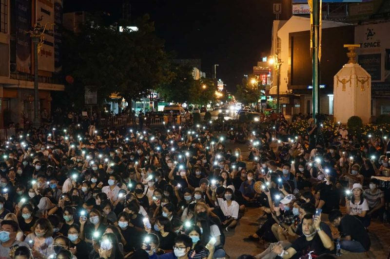 Une foule de manifestants, assis au sol, de nuit. Chacun a allumé la torche de son téléphone portable.