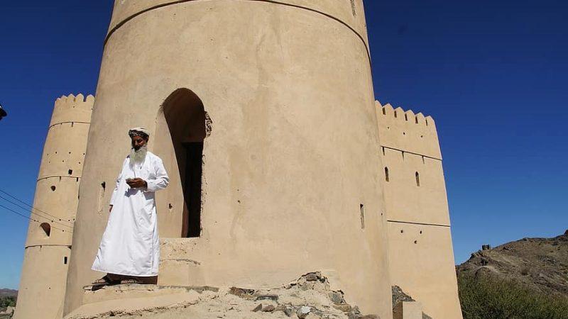 Un homme en burnous blanc et portant une longue barbe se tient devant un bâtiment fortifié à Oman.