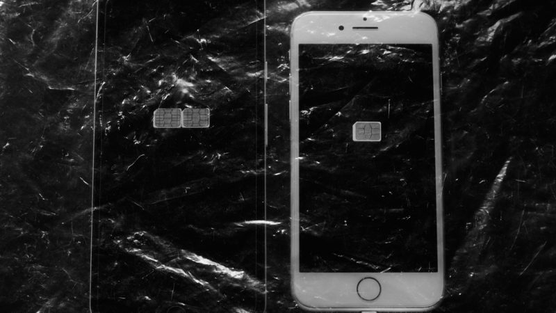 Un téléphone mobile dont la carte SIM a été retirée est présenté sous un film plastique.