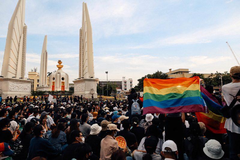 Une foule compacte est massée près du monument de la démocratie à Bangkok. Des manifestants font flotter un drapeau arc-en-ciel.