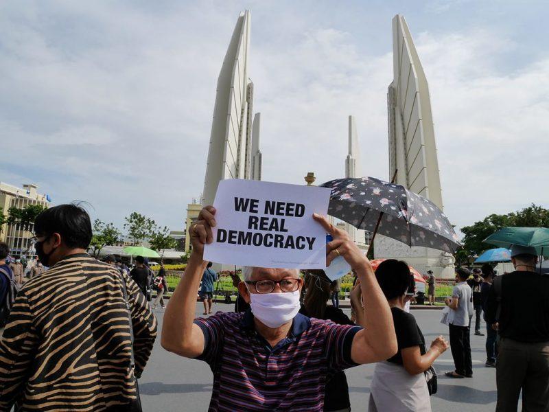 """Un homme âgé portant un masque tient une feuille de papier sur laquelle est écrit en anglais : """"Nous avons besoin d'une vraie démocratie""""."""