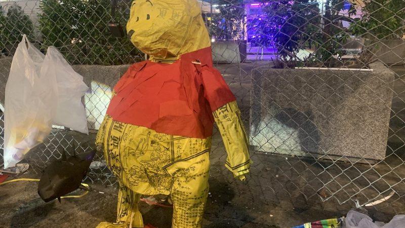 Winnie l'ourson, fabriqué en papier mâché. Sur le papier, on peut lire des caractères chinois. Le personnage porte un haut rouge et se tient debout devant un grillage.